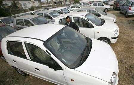 A man walks among parked vehicles at a card yard in Jammu December 10, 2012. REUTERS/Mukesh Gupta