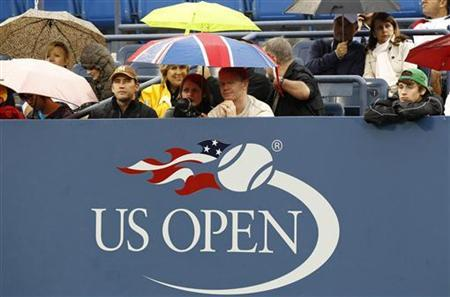 Fans wait for play to be resumed during a rain delay in the women's doubles final match between Vania King of the U.S. and Yaroslava Shvedova of Kazakhstan against Liezel Huber of the U.S. and Nadia Petrova of Russia during the U.S. Open tennis tournament in New York, September 12, 2010. REUTERS/Kevin Lamarque/Files
