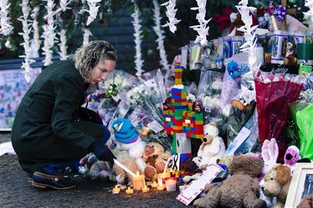 A woman lights candles while visiting a memorial to the victims of the recent shooting in Sandy Hook Village in Newtown, Connecticut December 17, 2012. REUTERS/Lucas Jackson
