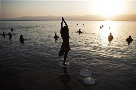 A woman practices yoga during a mass floating event in the Dead Sea September 14, 2012. REUTERS/Nir Elias