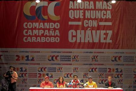 Venezuela's Vice President Nicolas Maduro (C) talks during a news conference of the United Socialist Party of Venezuela (PSUV) in Caracas December 16, 2012. The banner reads: 'now more than ever we are with Chavez'. REUTERS/Edwin Montilva