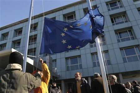 Municipal workers pull down from a pole a European flag during a rally against state sector layoffs demanded by the country's international lenders in Athens December 13, 2012. The German government is in favour of paying out the next tranche of international aid to Greece after a successful debt buyback programme by Athens, Germany's finance ministry said in a letter seen by Reuters on Wednesday. REUTERS/John Kolesidis (GREECE - Tags: CIVIL UNREST POLITICS BUSINESS)