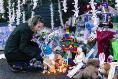 Una donna accende una candela davanti in omaggio delle piccole vittime uccise da un folle in una scuola di Newtown. REUTERS/Lucas Jackson