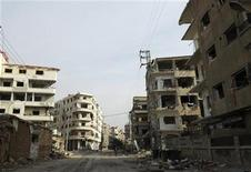 A man walks on a damaged street in Daraya near Damascus December 16, 2012. Picture taken December 16, 2012. REUTERS/Hussam Chamy (SYRIA - Tags: CONFLICT CIVIL UNREST)