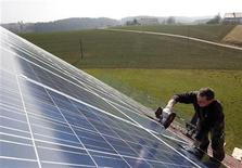 A worker mounts 320 square metres of solar panels on the roof of a farmstead barn in Binsham near Landshut March 21, 2012. German government plans cuts in the solar funding. REUTERS/Michaela Rehle (GERMANY - Tags: POLITICS BUSINESS ENERGY ENVIRONMENT)