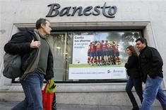 Banco Santander presentó el lunes a los accionistas minoritarios de Banesto una oferta de canje para hacerse con el 100 por cien de su filial y despejar el camino para adelgazar su negocio de banca al por menor en España, muy lastrado por la dura crisis que atraviesa el país. En la imagen, varias personas pasan junto a una sucursal de Banesto en Madrid el 17 de diciembre de 2012. REUTERS/Andrea Comas