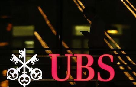 An employee uses a mobile phone as he walks past the logo of Swiss bank UBS in Zurich December 17, 2012. UBS AG will pay around $1.5 billion to settle charges that a group of traders at its Japanese unit rigged Libor interest rates, a source familiar with the matter said on Monday as the Swiss bank prepares for a deal with regulators. REUTERS/Michael Buholzer (SWITZERLAND - Tags: BUSINESS LOGO)