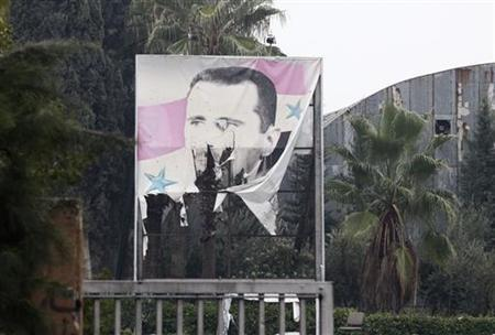 A torn poster of Syria's President Bashar al-Assad is seen at the entrance of a factory in Ouwayjah village in Aleppo December 17, 2012. REUTERS/Zain Karam