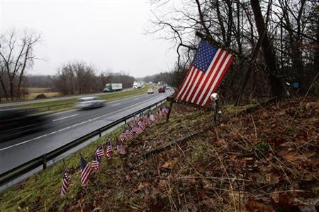 Traffic moves past a memorial of 27 small U.S. flags, for victims of a shooting at Sandy Hook Elementary School, along Interstate 84 in Newtown, Connecticut December 17, 2012. REUTERS/Joshua Lott
