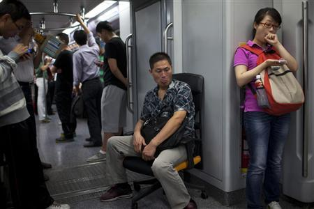 A man sits on an office chair while riding the subway train in Shanghai in this September 20, 2012 file photo. REUTERS/Aly Song/Files