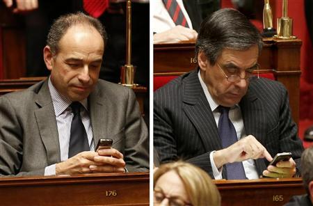 Combo picture shows French UMP political party head and deputy Jean-Francois Cope (L) and Francois Fillon (R), head of the R-UMP (Rally for the UMP) parliamentary faction and former candidate for the leadership of the UMP political party, using their mobile phones during the questions to the government session at the National Assembly in Paris December 4, 2012. Cope and Fillon were meeting for a second day to try and resolve a two-week standoff that has clouded the UMP's future. REUTERS/Charles Platiau