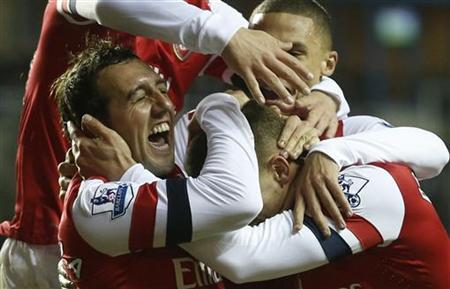 Arsenal's Santi Cazorla (L) celebrates with team mates after scoring a hat trick against Reading during their English Premier League soccer match at the Madejski stadium in Reading, southern England December 17, 2012. REUTERS/Eddie Keogh
