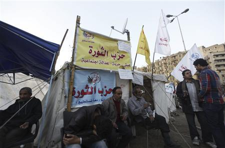 Protesters against Egypt's President Mohamed Mursi rest in front of a tent named ''Revolution Party'' at Tahrir Square in Cairo December 17, 2012. Egypt's opposition called for nationwide protests against a constitution backed by Mursi, after a vote exposed deep divisions that could undermine his efforts to build consensus for tough economic measures. REUTERS/Amr Abdallah Dalsh