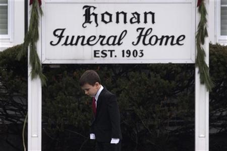 A boy stands outside a funeral home where services for six-year-old Jack Pinto, one of 20 schoolchildren killed in the December 14 shootings at Sandy Hook Elementary School, were being held in Newtown, Connecticut December 17, 2012. REUTERS/Adrees Latif