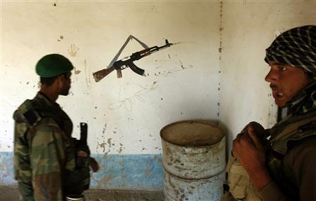 Afghan soldiers look at a painting of a Kalashnikov rifle on a wall as they search a house for weapons in Dorfshan river valley in Uruzgan province, in this November 7, 2007 file picture. Arms purchases are soaring in Afghanistan, along with the price of weapons, a sign that many Afghans fear a return of the Taliban, civil war or rising lawlessness. Afghanistan wants to project an image of stability ahead of 2014, a critical year when presidential elections will be held and the 350,000 Afghan security force will take over security from Western troops. REUTERS/Goran Tomasevic
