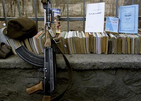 A Kalashnikov lies near a pile of books in Kabul, in this February 22, 2002 file picture. Arms purchases are soaring in Afghanistan, along with the price of weapons, a sign that many Afghans fear a return of the Taliban, civil war or rising lawlessness. Afghanistan wants to project an image of stability ahead of 2014, a critical year when presidential elections will be held and the 350,000 Afghan security force will take over security from Western troops. REUTERS/Mario Laporta/Files