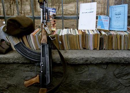 A Kalashnikov lies near a pile of books in Kabul February 22, 2002. REUTERS/Mario Laporta/Files