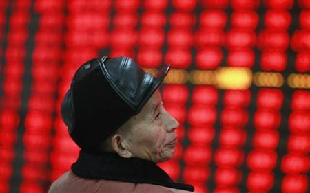 An investor reacts in front of an electronic board showing stock information at a brokerage house in Huaibei, Anhui province December 14, 2012. REUTERS/Stringer