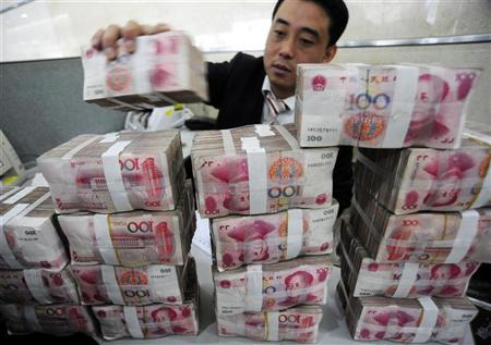 An employee counts Renminbi banknotes at a Bank of China branch in Hefei, Anhui province November 17, 2009. REUTERS/Stringer/Files