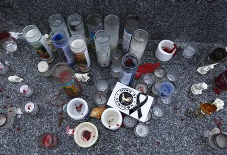 Candles and a sticker are seen honoring the victims of the Sandy Hook Elementary school shootings in Newtown, Connecticut December 17, 2012. The small Connecticut town shattered by an act President Barack Obama called ''unconscionable evil,'' holds on Monday the first two of 20 funerals for schoolchildren massacred in their classrooms last week. REUTERS/Shannon Stapleton (UNITED STATES - Tags: CRIME LAW EDUCATION)