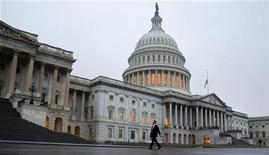 "A man walks past the U.S. Capitol Building in Washington December 17, 2012. The first real movement in the ""fiscal cliff"" talks began on Sunday, with Republican House Speaker John Boehner edging slightly closer to President Barack Obama's key demands as they try to avert the steep tax hikes and spending cuts set to take effect unless Congress intervenes by December 31. REUTERS/Joshua Roberts (UNITED STATES - Tags: POLITICS BUSINESS)"