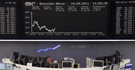 Traders are pictured at their desks in front of the DAX board at the Frankfurt stock exchange September 19, 2011. REUTERS/Remote/Amanda Andersen/Files