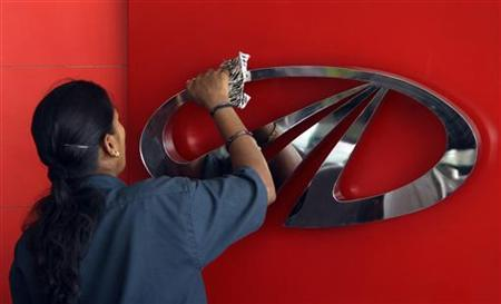A worker cleans a logo of Mahindra & Mahindra, India's largest utility vehicles maker, inside their showroom in the southern Indian city of Chennai April 12, 2011. REUTERS/Babu