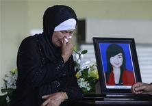 Мать одной из жертв катастрофы Sukhoi Superjet 100 на траурной церемонии в Джакарте 23 мая 2012. Пилот российского лайнера Sukhoi Superjet 100 проигнорировал сообщения системы предупреждения о встрече с землей, что привело к катастрофе и гибели всех 45 человек на борту, заявила Национальная комиссия по безопасности транспорта Индонезии. REUTERS/Beawiharta