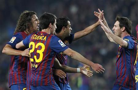 (L-R) Barcelona's Carles Puyol, Isaac Cuenca, Xavi Hernandez and Lionel Messi celebrate a goal against Getafe during their Spanish First division soccer match at Camp Nou stadium in Barcelona, April 10, 2012. REUTERS/Albert Gea