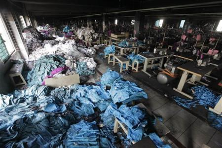 Piles of clothes are seen alongside sewing machines in the Tazreen Fashions garment factory, where 112 workers died in a devastating fire last month, in Savar November 30, 2012. REUTERS/Andrew Biraj