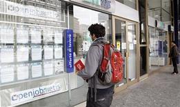 Un giovane guarda le offerte di un'agenzia di lavoro a Milano. REUTERS/Alessandro Garofalo