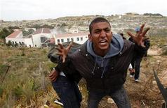 """Amnistía Internacional ha condenado lo que considera explotación """"endémica y generalizada"""" de trabajadores inmigrantes en Italia e instó al Gobierno a mejorar sus políticas de inmigración. En la imagen de archivo, un tunecino escapado de los disturbios en Túnez abandona el centro de inmigrantes de la isla italiana de Lampedusa en abril de 2011 para evitar ser devuelto a su país. REUTERS/Antonio Parrinello"""