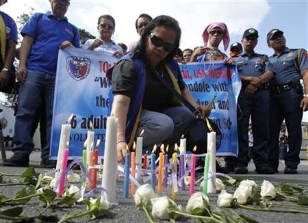 A Filipino human rights activist lights candles and offers prayers for victims, who were killed in a shooting at Sandy Hook Elementary School in Newtown, Connecticut in the U.S., during a prayer vigil in front of the U.S. embassy in Manila December 18, 2012. REUTERS/Romeo Ranoco (PHILIPPINES - Tags: CRIME LAW RELIGION)
