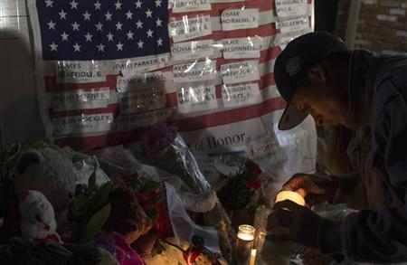 A man lights a candle in front of a flag with the names of victims who died in the December 14 shootings at Sandy Hook Elementary School in Sandy Hook village in Newtown, Connecticut, December 17, 2012. REUTERS/Adrees Latif