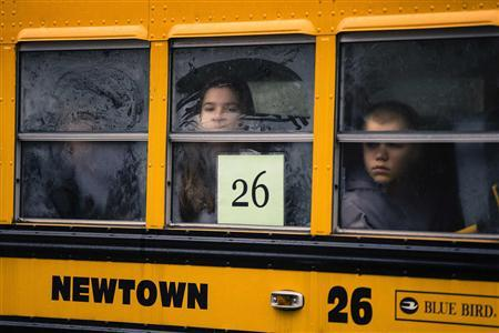Children look out through condensation on the windows of a school bus numbered 26 as it pulls into Newtown High School in Newtown, Connecticut December 18, 2012. REUTERS-Lucas Jackson