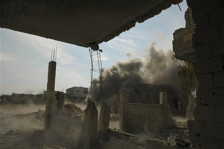 Smoke rises after what activists said was a strike by a tank shell during clashes with forces loyal to Syria's President Bashar al-Assad in Daraya near Damascus December 16, 2012. REUTERS/Hussam Chamy