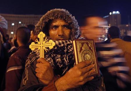 An anti-Mursi protester holds a Cross and a Koran at Tahrir Square in Cairo December 12, 2012. REUTERS/Khaled Abdullah/Files