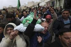 Palestinians carry the body of teenager Mohamad Salaymeh during his funeral in the West Bank city of Hebron in this December 13, 2012 file photo. REUTERS/Ammar Awad/Files