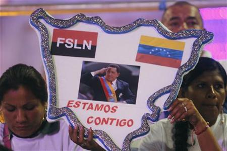 Members of Juventud Sandinista (Sandinista Youth) hold a poster in the shape of Nicaragua with a photo of Venezuela's President Hugo Chavez, during a concert for the health of Chavez at the Revolution Square in Managua December 17, 2012. REUTERS/Oswaldo Rivas