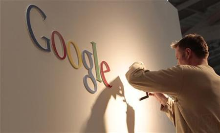 A man works on Google logo at an exhibition stand at the CeBIT computer fair in Hanover February 28, 2011. REUTERS/Tobias Schwarz