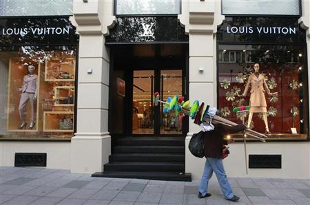 A street vendor walks past a Louis Vuitton luxury boutique in Istanbul November 20, 2012. REUTERS/Osman Orsal