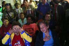 Supporters of Venezuelan President Hugo Chavez react while watching a government national TV broadcast with news about the president's health in Caracas in this December 14, 2012 file photograph. REUTERS/Jorge Silva/Files
