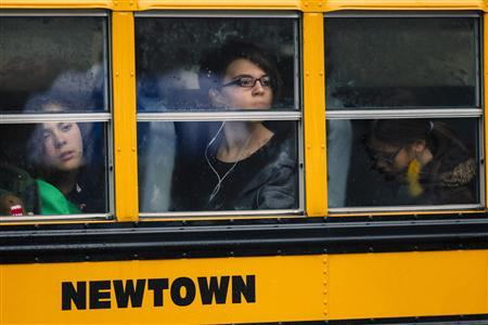 Students look out through condensation in the windows of a school bus as it pulls into Newtown High School in Newtown, Connecticut December 18, 2012. Students returned to school in the shattered Connecticut town of Newtown on Tuesday, accompanied by police and counsellors to help them cope with grief and fear after a gunman's shooting rampage killed 26 people at Sandy Hook Elementary School and altered attitudes about gun control in Washington. REUTERS/Lucas Jackson