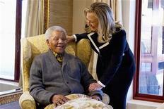"""Secretária de Estado norte-americana, Hillary Clinton, visita o ex-presidente da África do Sul, Nelson Mandela, na cidade sul-africana de Qunu, em agosto. Mandela está """"muito melhor"""" após ser tratado de uma infecção pulmonar e cálculos biliares, mas ele permanecerá no hospital por enquanto para cuidados extras, disse um porta-voz da Presidência sul-africana nesta terça-feira. 06/08/2012 REUTERS/Jacquelyn Martin/Pool"""