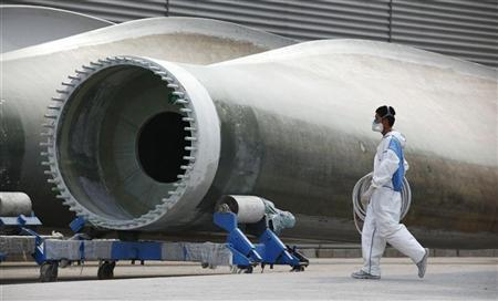 A worker wearing a gas mask walks past wind turbines outside the assembly workshop of the Guodian United Power Technology Company, at the city of Baoding, Hebei Province June 20, 2011. REUTERS/David Gray