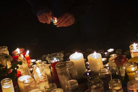 A girl lights a candle at a memorial for victims who died in the December 14 shootings at Sandy Hook Elementary School in Sandy Hook village in Newtown, Connecticut, December 17, 2012. REUTERS/Adrees Latif