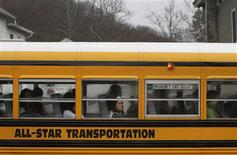 Students on a school bus look at a memorial for the victims of Sandy Hook Elementary School in Newtown, Connecticut December 18, 2012. REUTERS/Joshua Lott