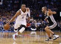 Russell Westbrook d'Oklahoma (à gauche) face à Tony Parker des Spurs. Le Thunder d'Oklahoma City a remporté lundi le choc de la Conférence Ouest de la NBA en s'imposant 107-93 sur son parquet face aux San Antonio Spurs. /Photo prise le 18 décembre 2012/REUTERS/Bill Waugh