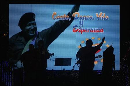 A band is silhouetted as they perform at Revolution Square, during a concert for the health of Venezuela's President Hugo Chavez, in Managua December 17, 2012. The words on the screen read as ''Sing, Dance, Life and Hope''. REUTERS/Oswaldo Rivas