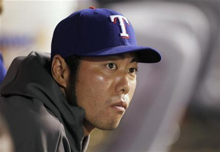 Texas Rangers relief pitcher Koji Uehara of Japan, who is currently on the disabled list, sits in the dugout against the Los Angeles Angels during the ninth inning of an MLB American League baseball game in Anaheim, California July 20, 2012. REUTERS/Danny Moloshok